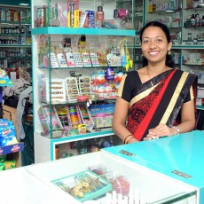 Woman selling at counter in a shop in rural India.